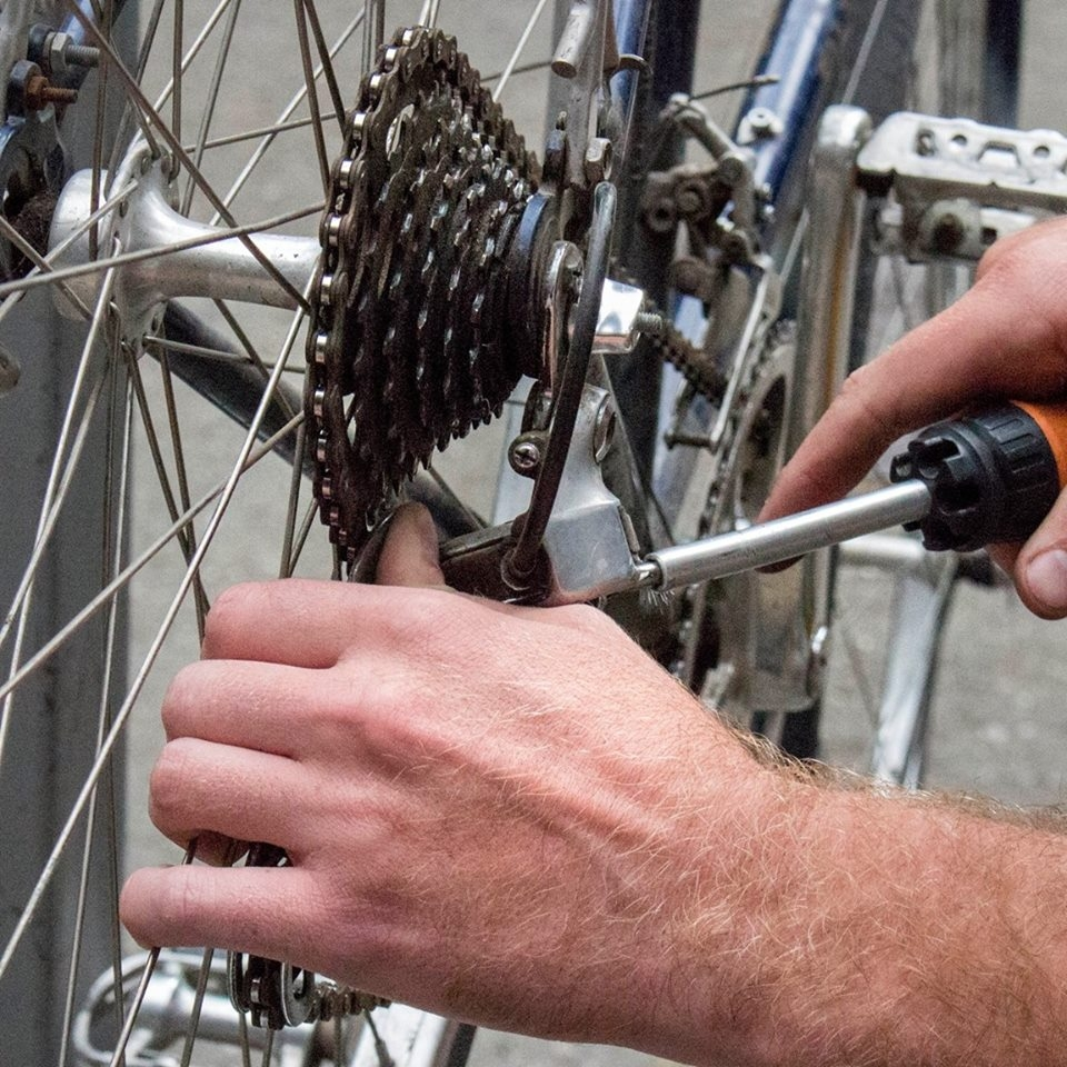 A student adjusting their rear derailleur's lower limit screw.